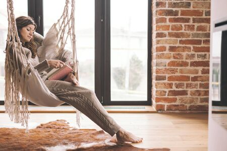 Beautiful young woman, which is wearing cashmere nightwear clothes, reading novel on rocking chair in scandinavian cabin one lazy weekend morning