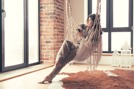 Beautiful young woman, which is wearing cashmere nightwear clothes, drinking tea or coffee while relaxing on hammock in scandinavian cabin near big window one lazy weekend morning