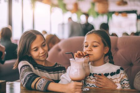 Children drink smoothie in family cafe. Two little friends celebrating birthday party in indoor restaurant.