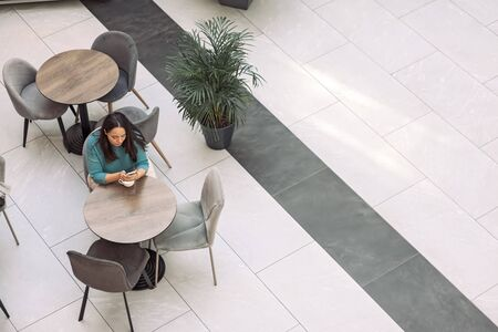 Beautiful plus size woman using smartphone while spending time in cafe inside shopping mall