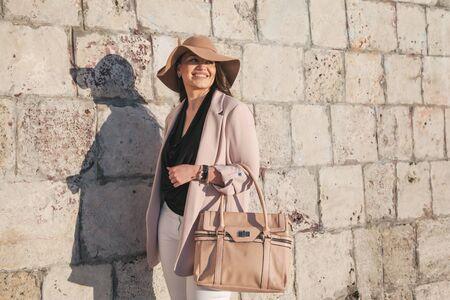 Giovane donna alla moda che indossa blazer, cappello e borsetta neutri che camminano per le strade della città in primavera. Moda casual, look elegante. Modello taglie forti. Archivio Fotografico