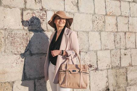 Young stylish woman wearing neutral blazer, hat and handbag walking on the city street in spring. Casual fashion, elegant look. Plus size model. Imagens
