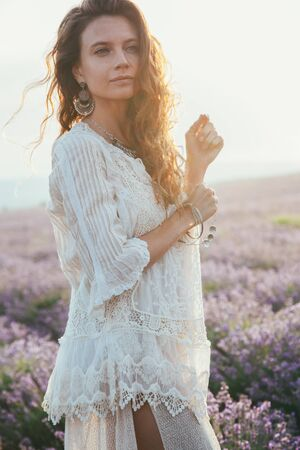Beautiful model walking in spring or summer lavender field in sunrise sunshine. Boho style clothing and silver jewelry. Фото со стока