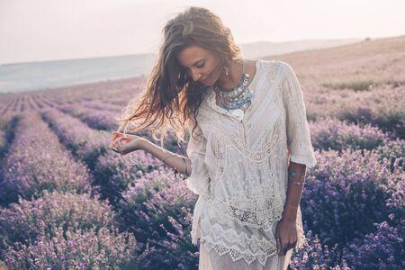 Hermosa modelo caminando en el campo de lavanda de primavera o verano en el sol del amanecer. Ropa de estilo boho y bisutería de plata.