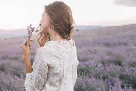 Hermosa modelo caminando en el campo de lavanda de primavera o verano en la salida del sol a contraluz. Ropa y bisutería estilo boho. Foto de archivo