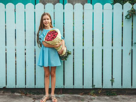 Tween girl holding a bunch of pink roses wrapped in craft paper over blue wooden fence 免版税图像