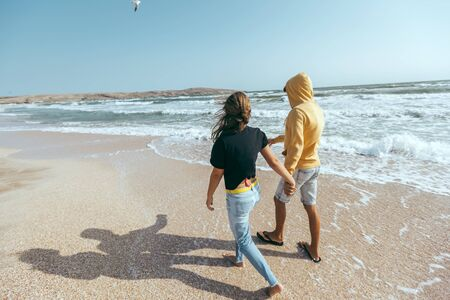 Back view of teenage boy and girl holding hands while walking on the beach. First love, romantic scene, positive feelings. Stock fotó