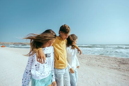 Group of happy teenage friends travelling to the beach. Hipster boy and girls wearing fashion teen clothes, having fun while walking outdoor.