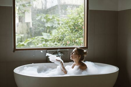 Woman relaxing with pleasue in foam bath with bubbles in modern hotel dark bathroom by big window with tropical view