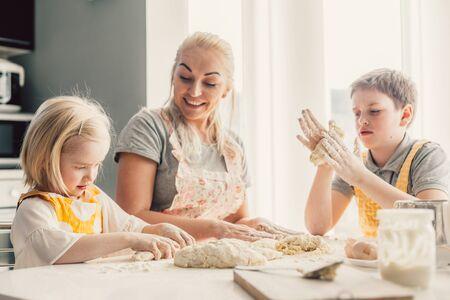 Schöne blonde Mutter, die ihren zwei Kindern das Kochen auf der Küche beibringt. Eltern machen tägliches Frühstück zusammen mit Kindern. Lebensstilfoto der Familie zu Hause.