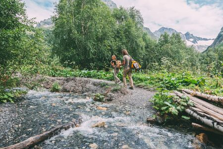 Family hikers with backpacks crossing river on log by forest, father with child
