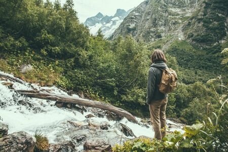 Man traveler alone with backpack standing and looking at mountain river or small waterfall among green woods.