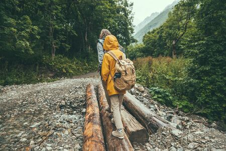 Hikers with backpacks crossing river on log by forest, father with child, rain weather