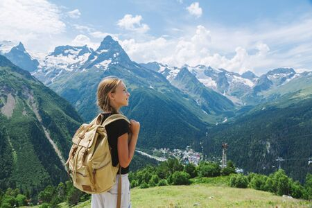 Child girl traveler with backpack standing on mountain hill and enjoying amazing summer view.