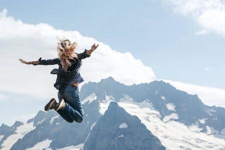 Frauenwanderer, die über blauen Himmel, Freiheit und Freude auf den Berg springen