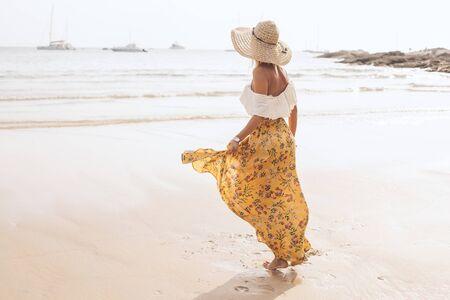 Girl wearing floral maxi skirt walking barefoot on the sea shore, Thailand, Phuket. Bohemian clothing style. Фото со стока