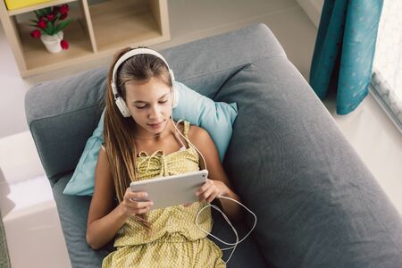 Pre teen child playing tablet and listening to music in head phones while relaxing on couch in living room at home, top view.