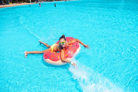 Teen girl relaxing on the inflatable ring in water in the aqua park in Thailand