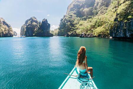 Rückansicht des jungen Mädchens, das sich auf dem Boot entspannt und die Insel betrachtet. Reisereise nach Lagune in Asien: El Nido, Palawan, Philippinen.
