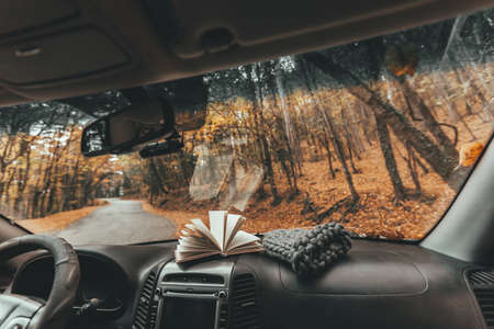 Fall trip looking inside of car. Book and knitted hat on windshield. Freedom travel concept. Autumn weekend to the forest.