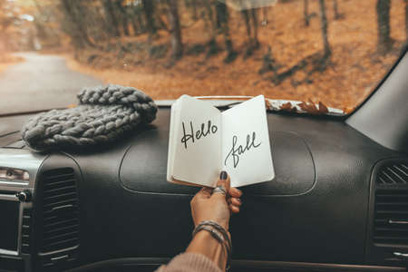 Fall trip looking inside of car. Woman hand holding notebook with Hello Fall text over windshield. Freedom travel concept. Autumn weekend to the forest.