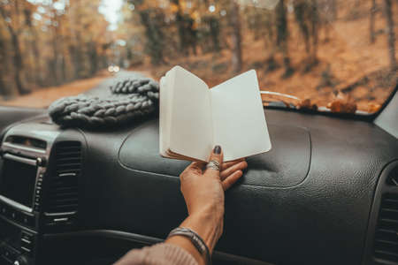 Road trip looking inside of car. Woman hand holding notebook with blank pages over windshield. Freedom travel concept. Autumn weekend to the forest. Standard-Bild