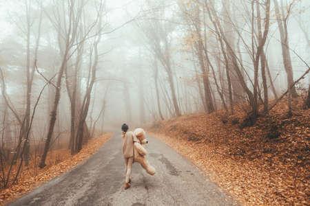 Woman with big plush teddy bear toy walking away on road in magic forest one foggy autumn day Standard-Bild