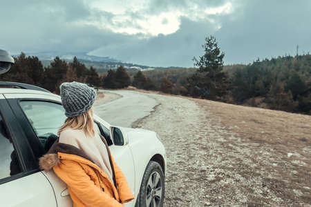 Woman standing by the car and looking away on road in mountains in cold bad weather