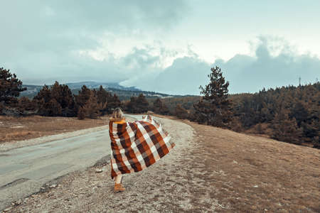 Woman wrapped in warm blanket standing on road and looking away in mountains in cold bad weather