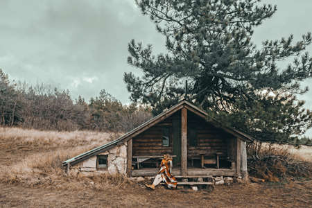 Woman resting in tiny hunter's getaway cabin while hiking in woods