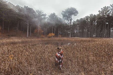 Woman traveller wrapped in plaid blanket relaxing by the lake in autumn in woods in cold fog weather