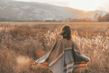 Girl in poncho travel alone in field with a view in sunlight. Warm autumn weather, calm scene. Wanderlust photo series. Standard-Bild - 157335994
