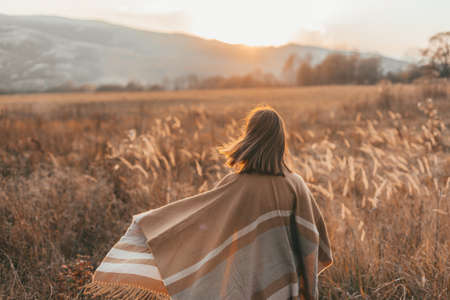 Girl in poncho travel alone in field with a view in sunlight. Warm autumn weather, calm scene. Wanderlust photo series.