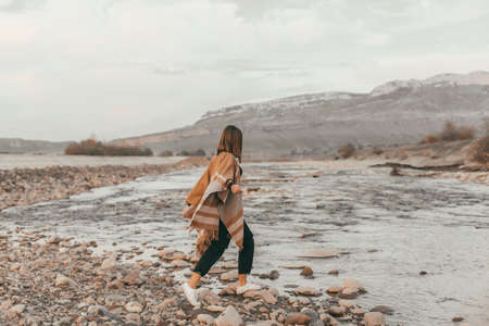 Girl in poncho travel alone by the mountain river. Warm autumn weather, calm scene. Wanderlust photo series.
