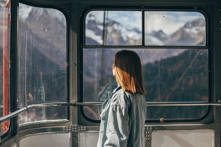 Young traveler looking at mountains view through sky lift window. Student girl spending her holidays in nordic country. Standard-Bild - 157335998