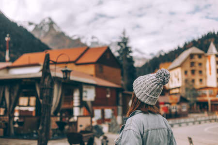 Teenage girl traveler standing and looking at village over mountains view. Student spending autumn or winter holidays in european places.