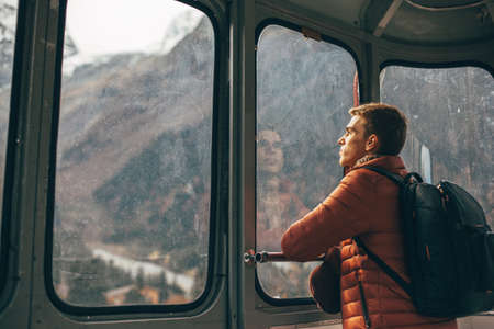 Young traveler with backpack looking at mountains view through sky lift window. Teenage guy spending his vacations in nordic country.