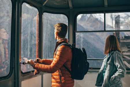 Two young travelers with backpack looking at mountains view through sky lift window. Teenage guy and girl spending their vacations in nordic country. Standard-Bild