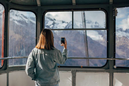 Young traveler taking photo of mountains on her smartphone through sky lift window. Student girl spending her holidays in nordic country.