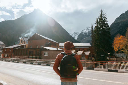 Teenage traveler standing and looking at village over mountains view. Student spending autumn or winter holidays in european countries. Standard-Bild - 157336008