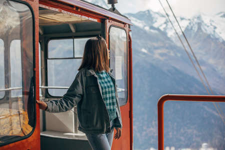 Young traveler looking at mountains view through sky lift window. Student girl spending her holidays in nordic country.