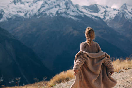 Woman walking in mountains enjoying beautiful landscape and feeling freedom and happiness. Autumn trip to nordic countries.