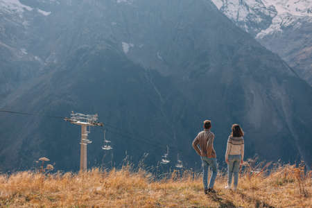 Two teenage friends dressed in warm fashion sweaters walking in mountains enjoying beautiful landscape and feeling freedom and happiness. Autumn trip to nordic countries. Standard-Bild