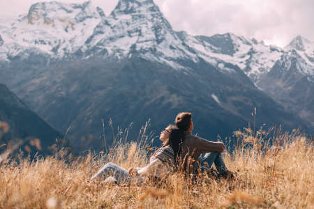 Two teenage friends dressed in warm fashion sweaters relaxing in mountains enjoying beautiful landscape and feeling freedom and happiness. Autumn trip to nordic countries.