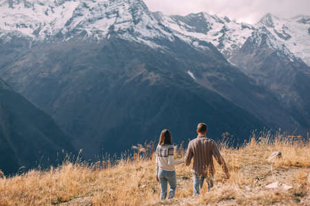 Two teenage friends dressed in warm fashion sweaters holding hands while walking in mountains enjoying beautiful landscape and feeling freedom and happiness. Autumn trip to nordic countries.