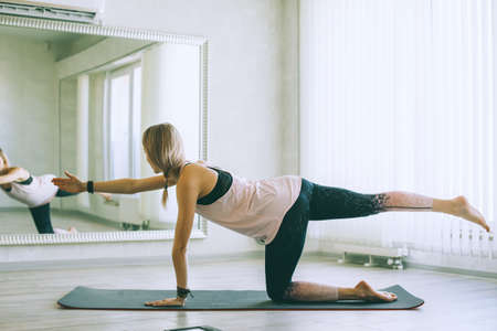 Young woman doing stretching exercise by mirror on floor mat in bright yoga class room. Standard-Bild - 157336088