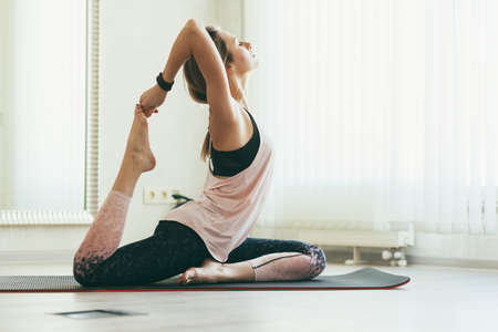 Young woman doing stretching exercise on floor mat in bright yoga class room.