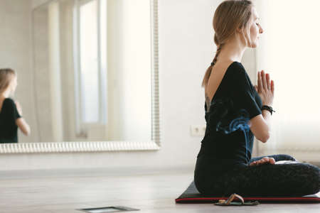 Young woman using aroma sticks while doing stretching exercise by mirror on floor mat in bright yoga class room.