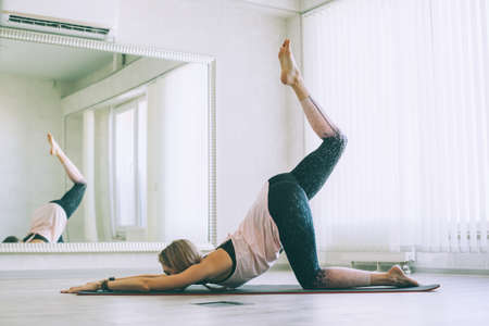 Young woman doing stretching exercise by mirror on floor mat in bright yoga class room.