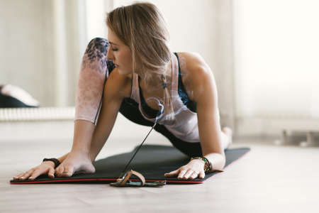 Young woman using aroma sticks while doing stretching exercise on floor mat in bright yoga class room. Standard-Bild